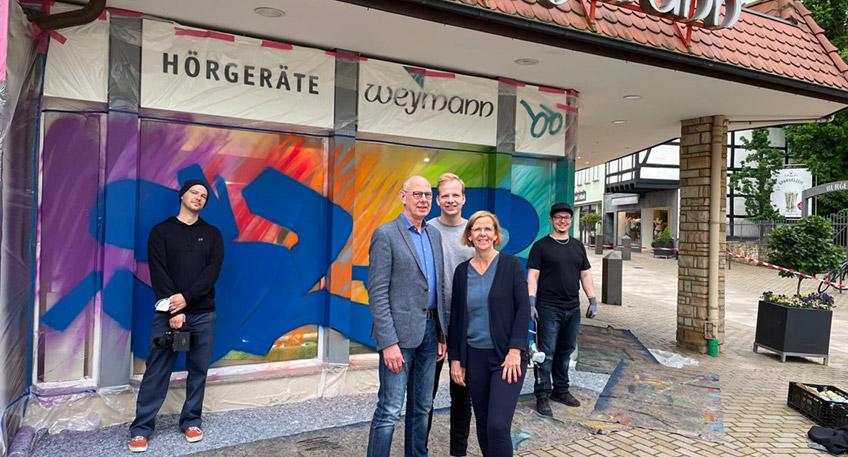 Seit gestern prangt an der Schaufensterfront vom Zentrum für Seh- und Hörberatung Weymann in Lübbecke ein farbenfrohes Graffiti. Mit dieser außergewöhnlichen Idee möchte sich Firmenchef Jörg Weymann bei der Lübbecker Bevölkerung für die Treue während der Corona-Zeit bedanken.