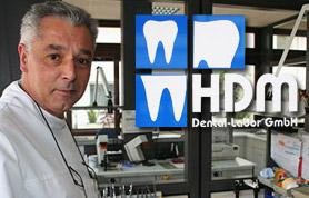 """Zähne sind ein Stück Lebensqualität, die nicht vernachlässigt werden sollten. Das ist der Leitsatz von Francesco Di Meo. Der Zahntechnikermeister ist Inhaber des HDM Dentallabors in Lübbecke, Am Markt 16b, das er in der Wiehengebirgsstadt seit 1988 führt. Das HDM-Dentallabor hat sich auf die Herstellung von Zahnersatz aller Art spezialisiert. Francesco Di Meo und seine Mitarbeiter arbeiten dabei mit Zahnärzten aus dem gesamten Kreis Minden-Lübbecke und Umgebung zusammen. Dabei setzt das Team Di Meo natürlich auf ausgereifte Technik auf neuesten Stand, um den Patienten Zahnersatz in hervorragender Qualität zu bezahlbaren Preisen anbieten zu können. Dennoch ist gerade bei Zahnersatzarbeiten höchste Präzision, vielfach auch in Handarbeit erforderlich, damit """"die Dritten"""" ideal passen, Schmerzen in Zukunft vermieden werden und natürlich auch ein kosmetisch vollkommenes Bild erreicht wird."""